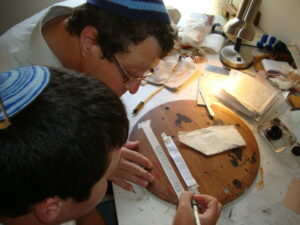 A boy participates in the Sofer Scribe Workshop helping to make his own Tefillin with Rabbi Steve Bar Yakov Gindi